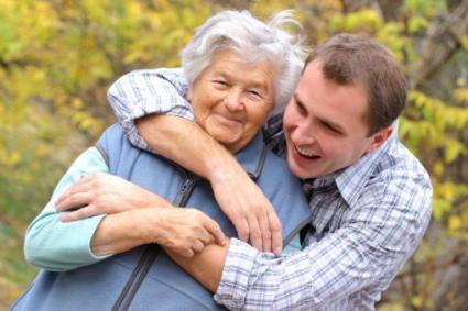Adult son hugging his senior mom