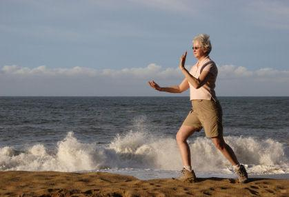 Senior woman practicing tai chi on the beach