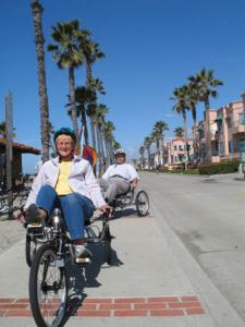 Senior couple riding recumbent bikes on the sidewalk