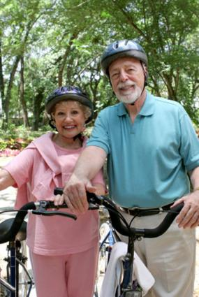 Senior couple wearing helmets bicycling in the park