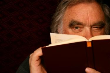 Senior man holding book close to read it