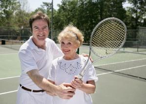 Tennis coach teaching an active senior woman