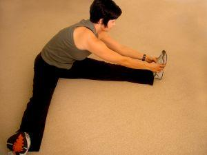 Woman sitting on floor and stretching