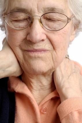 Elderly woman rubbing her painful neck
