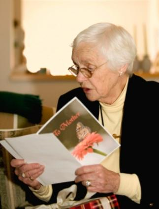 Senior woman reading a Mother's Day card and quote