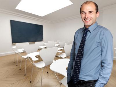 Happy male teacher in an empty classroom