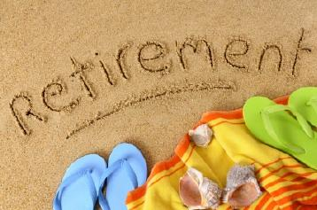 Beach towel, flip flops and retirement in the sand