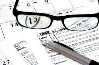 Glasses, tax form, and pen