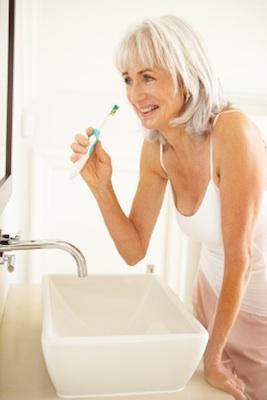 Senior woman brushing her teeth.