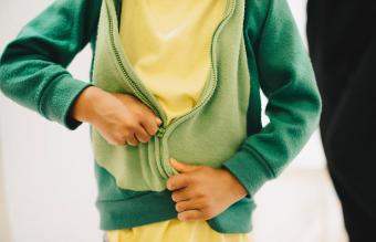 boy zipping his jacket at home