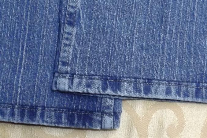 Hand-stitched jean hem.