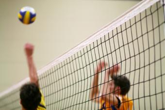 Young men in uniforms playing volleyball