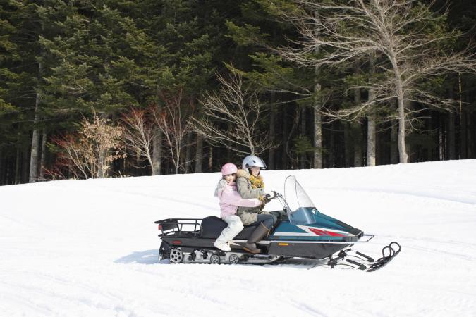 Mother and child riding on snowmobile