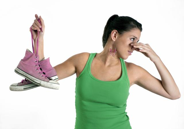 woman holding stinky shoes