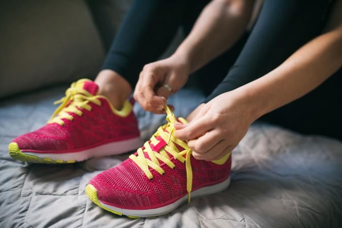 Woman putting on running pink shoes