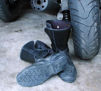 Motorcycle boots next to a tire