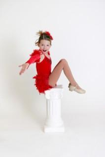 Child wearing red leotard and tap shoes