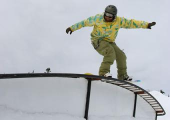 Snowboarder doing a nose press over a rainbow box