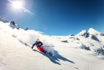 Skier doing turn in fresh powder snow
