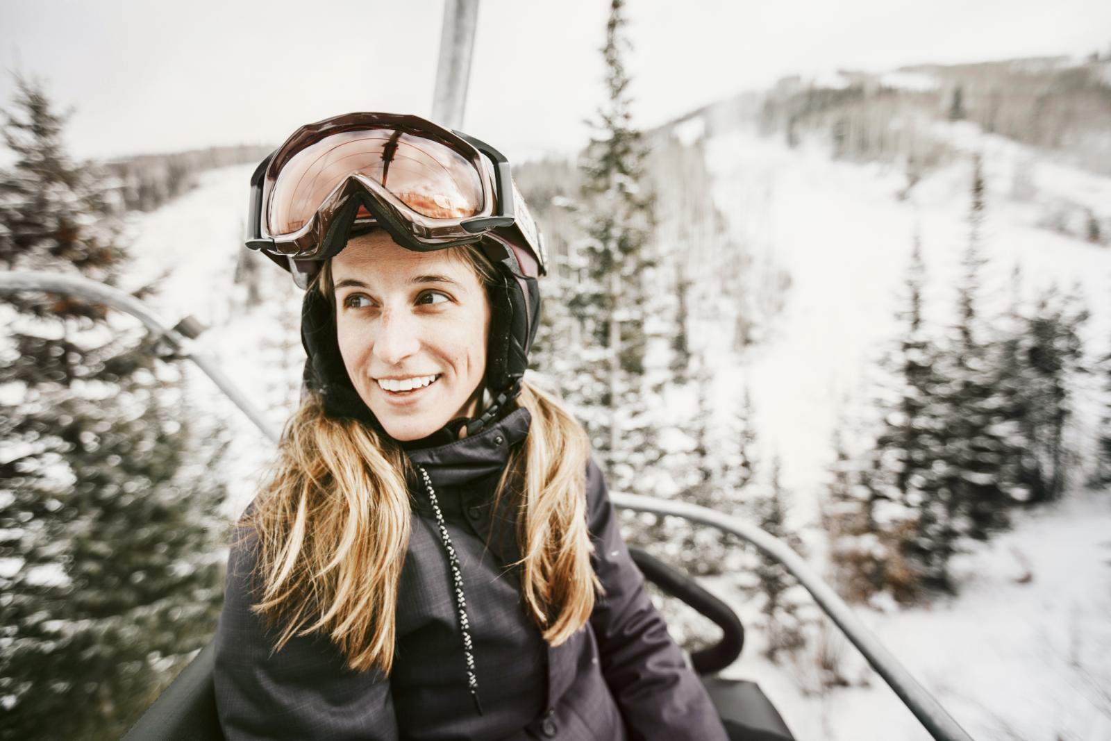Smiling woman riding ski lift