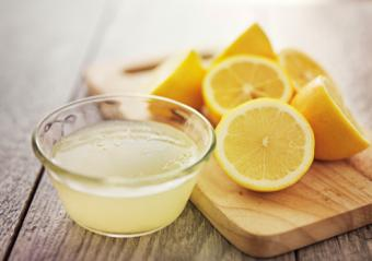 Cut lemons and a bowl of lemon juice