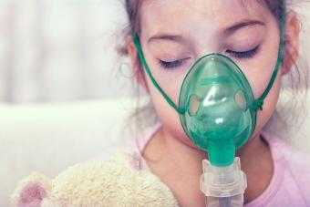 Young girl wearing an oxygen mask