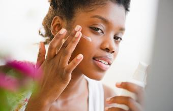 Woman putting on face lotion