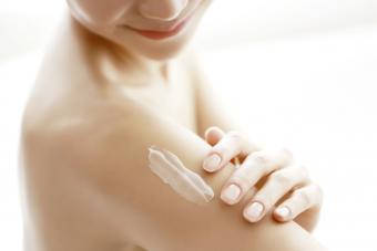 Woman applying body lotion on arm