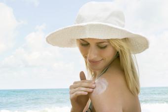 Woman putting suntan lotion on