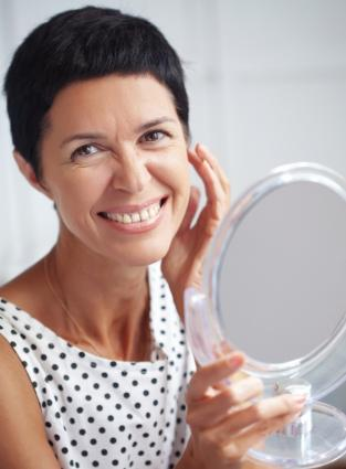 middle aged woman examining face
