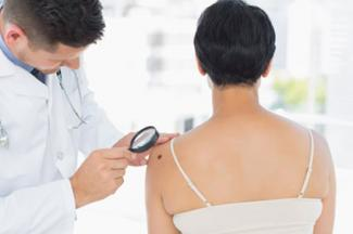 Dermatologist examining melanoma on woman