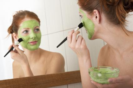 Woman applying green face mask