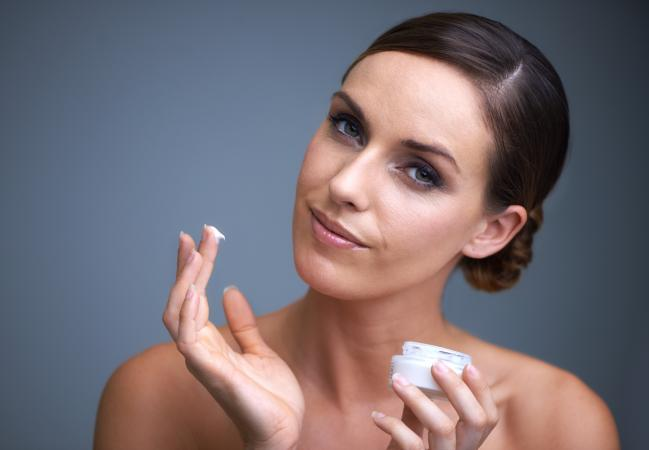 woman applying moisturizer to skin