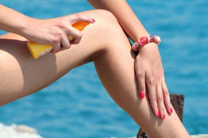 Woman applying sunscreen to her leg