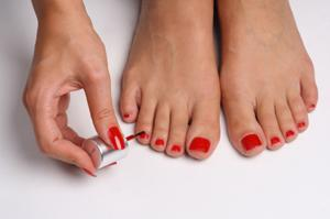 Image of a woman painting her toenails red