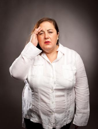 Tired, overweight woman with headache