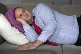 Business man sleeping on couch; © Wernerimages   Dreamstime.com