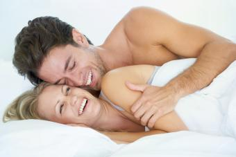 A husband embracing his wife affectionately while lying in bed together
