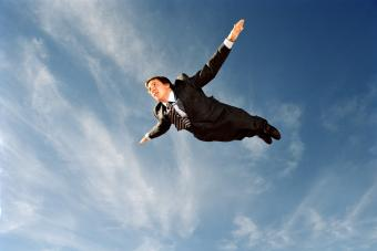 Young businessman flying through sky