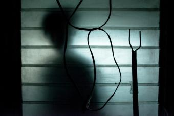 A silhouette of a person outside a window