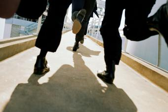 Men in black suits running on walkway, low angle view