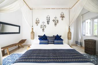 Cozy airy bedroom with blue pillows and dreamcatchers