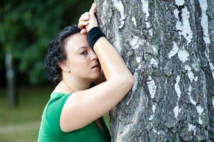 Exhausted woman leaning on tree; © Berc | Dreamstime.com