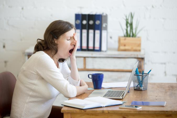 Sleepy woman yawning at desk