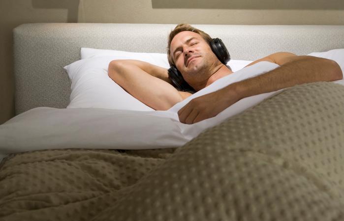Man sleeping in bed with headphones
