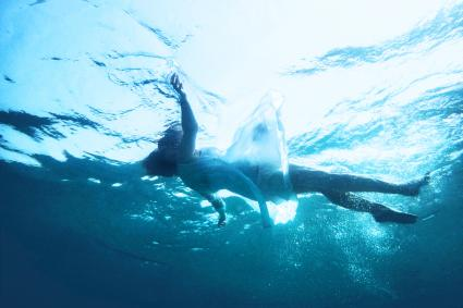 Dressed woman floating under the sea