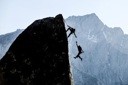 Rock climber reaching out to his partner who is falling