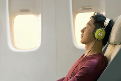 Man resting and listening to music on airplane