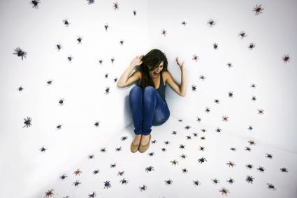 Young woman crouched in terror while surrounded by spiders