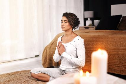 Young woman sitting and meditating with candles in her living room at home